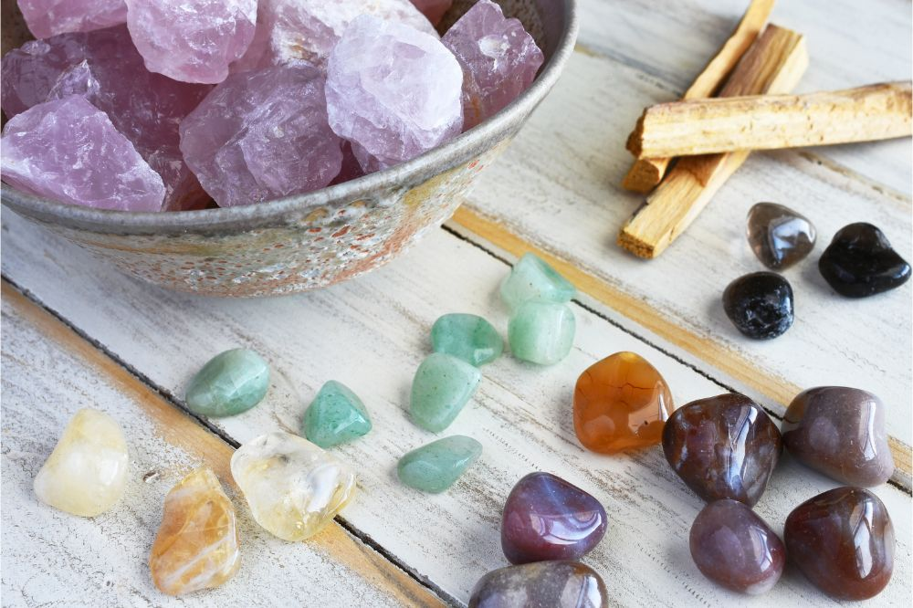 A top view image of rose quartz and various energy healing crystals on a white wooden table