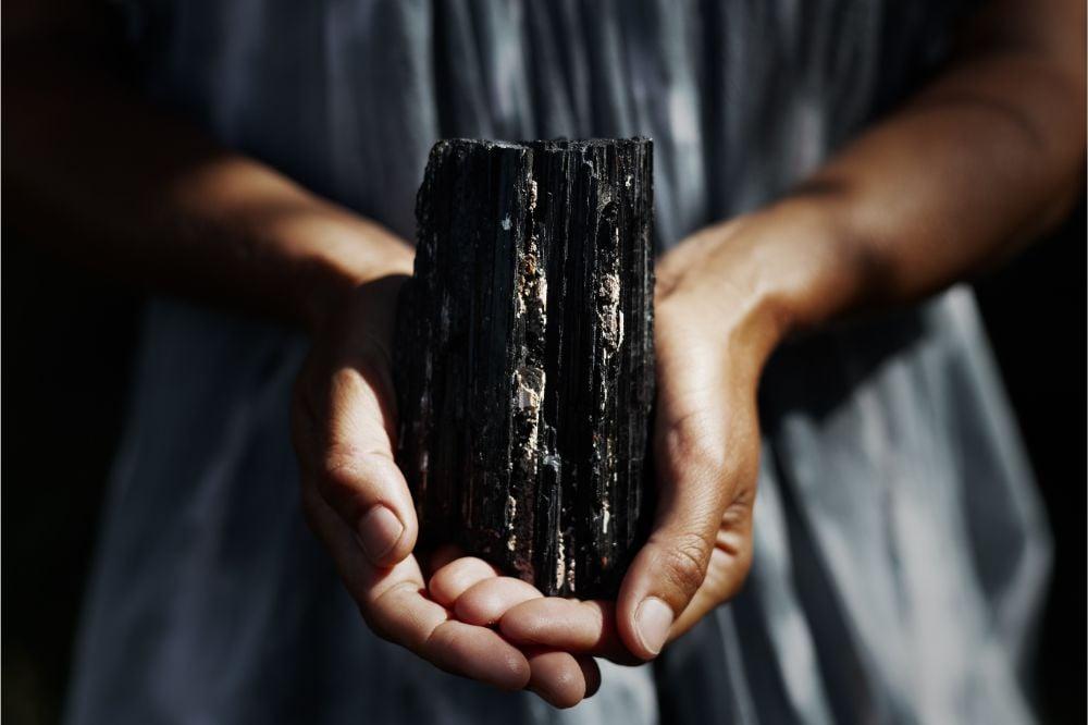 Woman's hands holding dark, powerful black tourmaline crystal