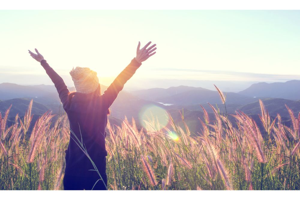 Happy Woman Enjoying Nature on grass meadow on top of mountain