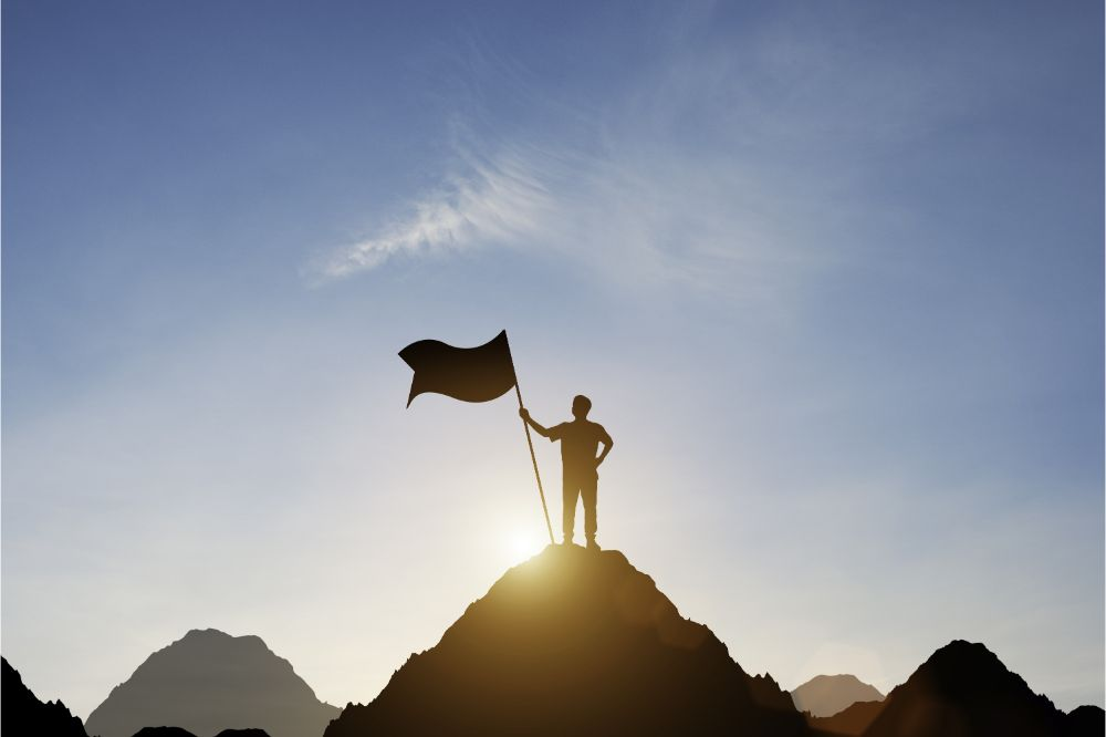 Silhouette of businessman holding flag on the top of mountain with over blue sky and sunlight