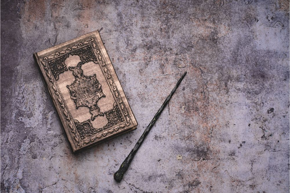 Old book with spells and magic wand on gray background