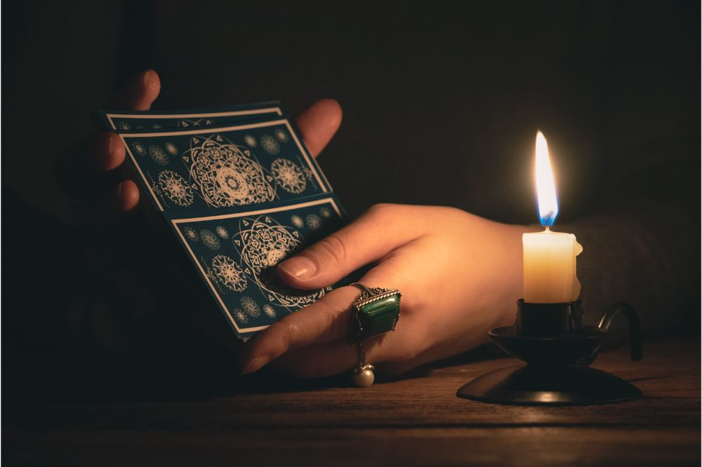 Fortune teller reading a future by tarot cards in the light of candle
