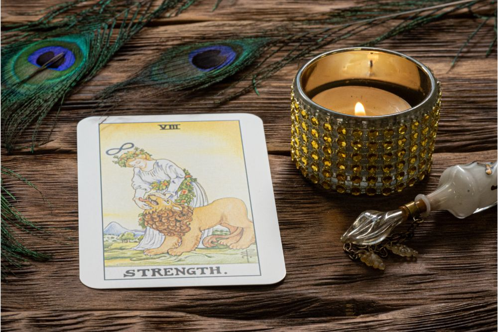 Strength tarot card on fortune teller wooden table background.