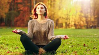 Young attractive female meditate in park.